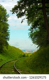 Old abandoned railroad among forested hills. Railway on country road through green forest. Summer rural beautiful landscape with rails among woodland trees