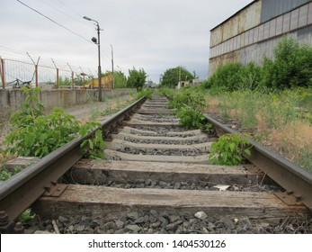 old abandoned railroad with rusty rails and rotting sleepers