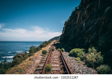 Old abandoned railway with a mountain on the right side and the ocean with waves on the left side in Wilderness, South Africa