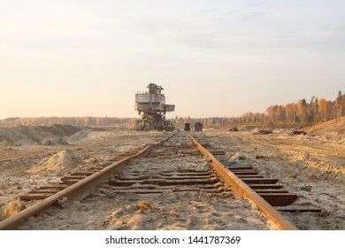 Old abandoned railway track. Rusty railroad tie. Giant stacker. Bucket chain excavator in a sand quarry. Bulk material handling