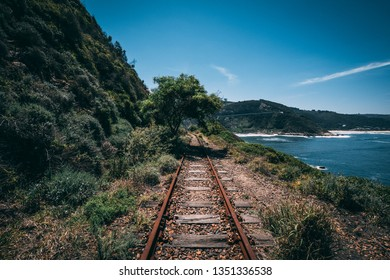 Old abandoned railway with a tree and a mountain on the left side and the ocean with a beach in the background in Wilderness, South Africa