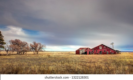 Old abandoned red barn on in the countryside. The colors are muted and sort of pastel in appearance. There are a few trees off the right. This is a 16x9 desktop crop aspect ratio.