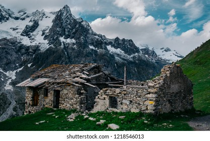 An old abandoned refuge with mountains in the background near refuge Bonatti on the Tour du Mont Blanc trail in Italy