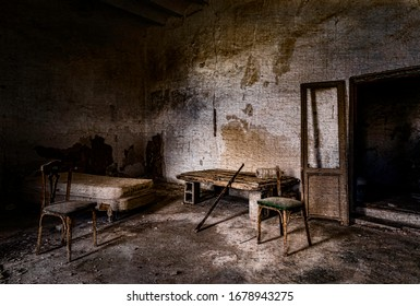 Old abandoned and ruined room with bed two chairs and bench