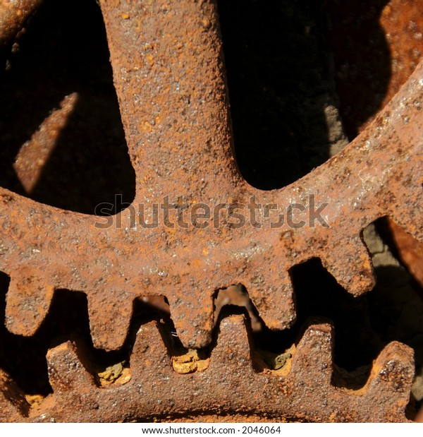 Old abandoned rusted gears next to building