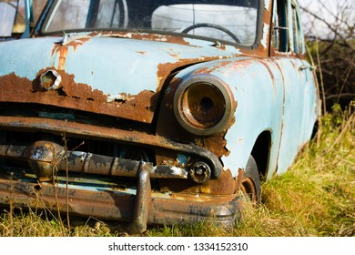 Old, abandoned rusty car wreck front and lamp.