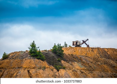 an old abandoned rusty excavator at the top of the quarry, an industrial quarry quarry no longer functions, a dead city, a ruinous place, a fir on the mountain