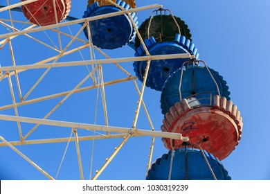 Old abandoned rusty ferris wheel in winter in a park with deep blue sky in the background