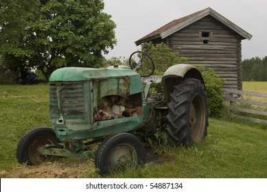 Old abandoned rusty tractor in front of Old farmer's wooden house museum Gamle Hvam. Norway.