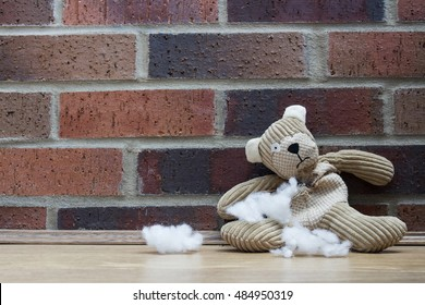 An old, abandoned and sad teddy bear with the stuffing falling from his ripped tummy and sitting on a cold, sparse wooden floor with a brick wall in the background.