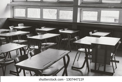 Old and abandoned school classroom interior, in black and white.