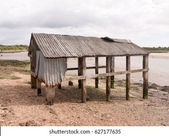 an old and abandoned sea shack shed decaying and rotting in the sun as seen from the side and back at the beach and seafront made of wooden and metal