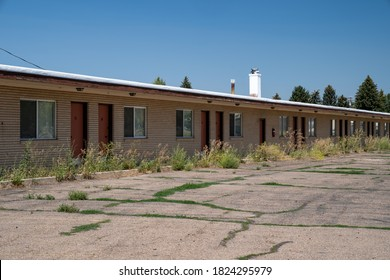 Old, abandoned seedy motorcourt style motel, decays in the sun. Weeds overgrowing in the parking lot