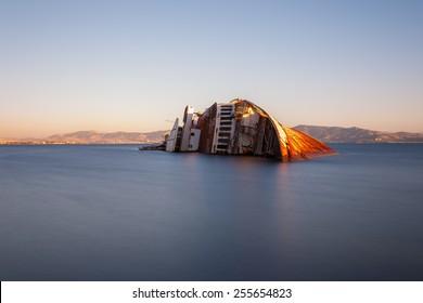 Old abandoned shipwreck near Elefsina, Greece against a colorful sky, long exposure photograph