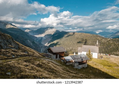 Old Abandoned storage barns and chapel on the wild meadows high above the Aletsch Glacier Valley National Park offering a view of the surrounding peaks, the glacier and the Wallis valley near Brig