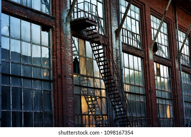 old abandoned textile factory building with large windows and fire escape stairs at sunset in Lodz,Poland