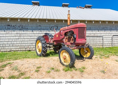 Old abandoned tractor in grass field by an abandoned barn.