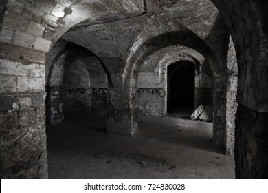 An old abandoned tunnel in an underground wine cellar. Entrance to catacombs. Dungeon of Old stone fortress. As creative background for dark creepy design. Mystical interior of ancient dungeon