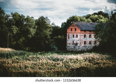 Old abandoned watermill surrounded by trees