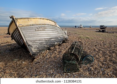 An old abandoned wooden fishing boat with lobster pots on a shingle beach with the sea and other boats in the background.