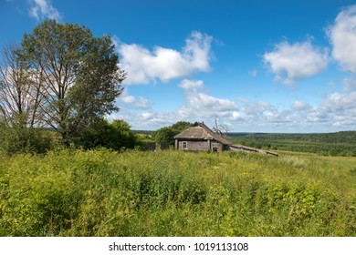 Old abandoned wooden house with green grass hills in the background