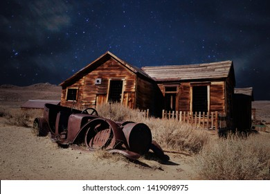 old abandoned wooden house and rusty car in the desert on starry night
