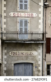 Old abandoned-looking building with inscription in French village