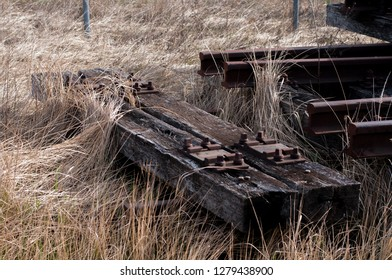 Old abandonned rusty rails with wooden sleepers in the dry old gras.
