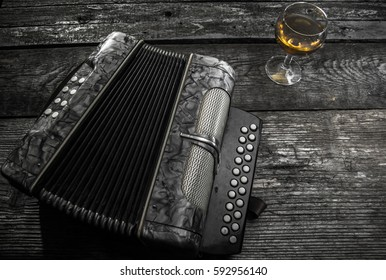 Old accordion on rustic wood table with wine