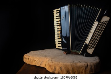 Old accordion on rustic wooden surface with black background and Low key lighting, selective focus.