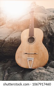 An old acoustic guitar resting on the rocks at sunset