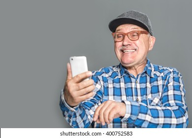 Old active man taking selfie with mobile phone isolated on grey background