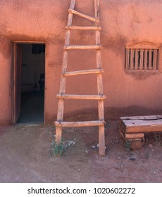 Old adobe, clay wall building exterior with narrow wooden ladder leaning against wall.