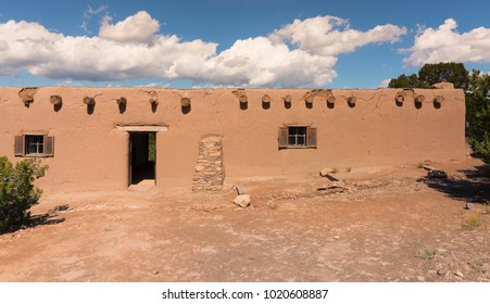 Old Adobe earthen, clay wall building set in southwest landscape with blue sky and white clouds in background.