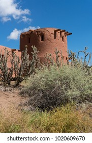 Old adobe tower fortress against bright blue skies with tall cholla cactus and desert shrubs in foreground.