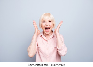 Old adult blonde glad excited cheerful astonished lady smiling, laughing, screaming, raising hands to cheeks, opened mouth, over grey background, isolated