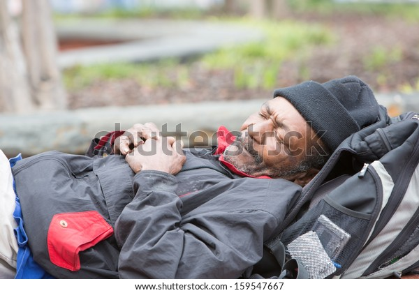 Old african american homeless man sleeping outside during the day.