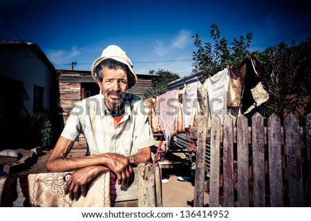 old african black man standing proudly in front of his home with washing on the line behind him