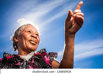 old african homeless lady in a floral shirt pointing with the bright sunny sky in the background