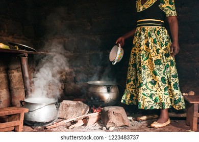 old african woman traditional cooking foufou in small village kitchen with smoke