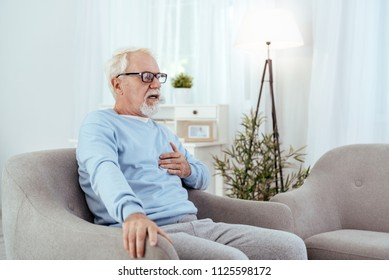 Old age. Alarmed senior man touching chest and posing in armchair
