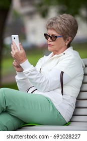 Old age Caucasian woman using cellphone, sitting on bench in park