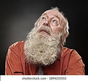 Old age concept. Portrait of an old man with white beard looking up expectantly. Black background. Religion and belief in God.