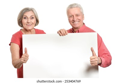 Old age couple holding blank banner ad against white background