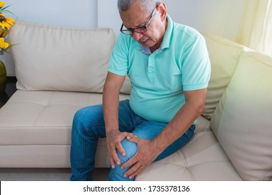 old age, health problem. Older man suffering from leg pain at home