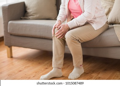 old age, health problem and people concept - close up of senior woman suffering from pain in leg at home