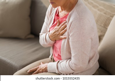 old age, health problem and people concept - close up of senior woman suffering from heartache at home