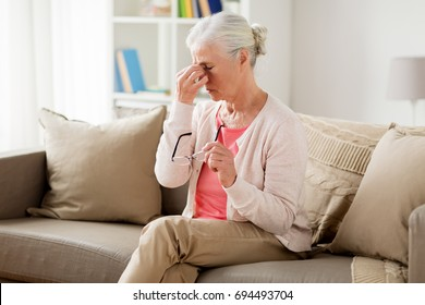 old age, health problem, vision and people concept - senior woman with glasses sitting on sofa and having headache at home