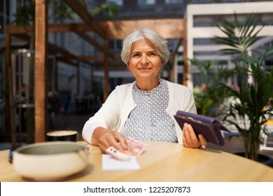 old age, leisure, payment and finances concept - happy senior woman with wallet and money paying bill for coffee and dessert at street cafe