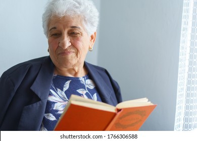 old age, leisure and people concept - senior woman sitting on sofa and reading red book at home. Elderly woman slavic appearance sitting in armchair study at home